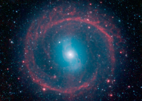 """It might look like as spoked wheel or even a """"Chakram"""" circular weapon wielded by television's fictional warrior Xena, but this ringed galaxy is actually a vast place of stellar life. A newly released image from NASA's Spitzer Space Telescope shows the ga"""